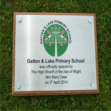 Silver aluminium plaque with full colour paint infill on a solid oak backing board