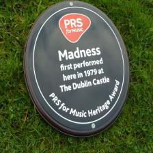 Round brass plaque, filled with black, red and white paint